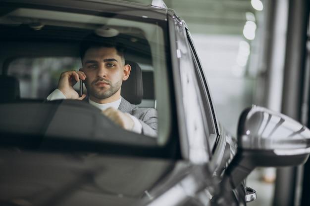 Uomo bello di affari che guida in automobile