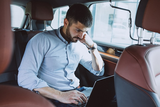 Uomo bello di affari che lavora ad un computer in automobile