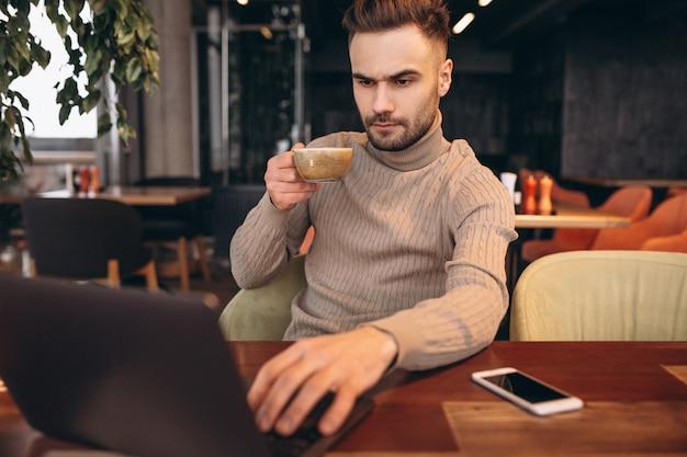 Uomo bello di affari che lavora al computer e che beve caffè in un caffè