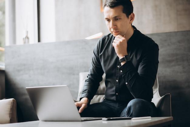 Uomo bello di affari che lavora al computer in ufficio