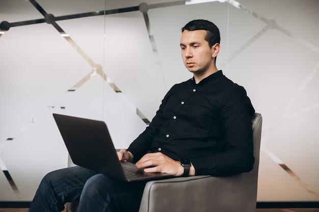 Uomo bello di affari che lavora con la compressa in ufficio