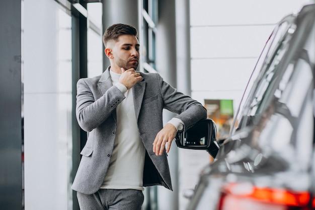 Uomo bello di affari che sceglie un'automobile in una sala d'esposizione dell'automobile