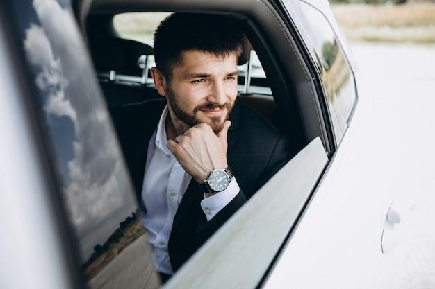Uomo bello di affari che viaggia in automobile