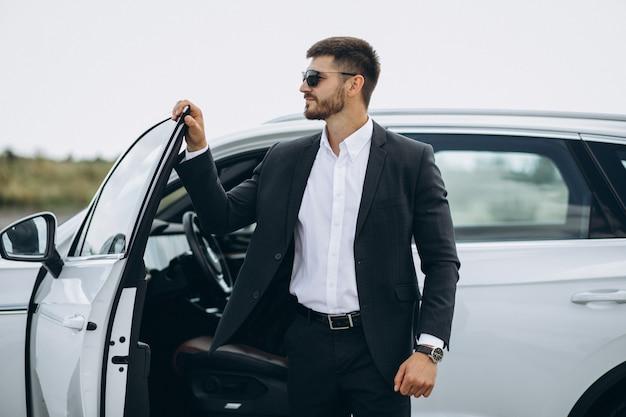 Uomo bello di affari in macchina bianca