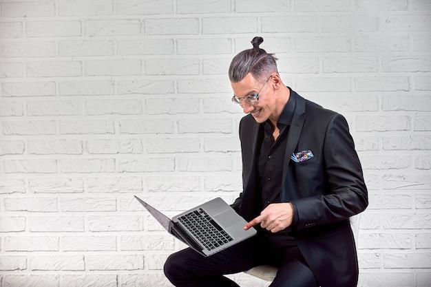 Uomo bello di affari in vetri e vestito che tiene il computer portatile in mano e scrivere qualcosa. vista laterale. su mattoni bianchi