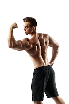 Uomo bello di altissimo livello muscolare che posa sul fondo bianco