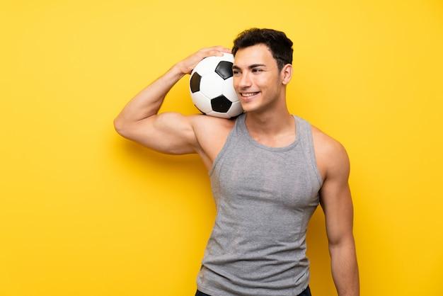 Uomo bello di sport sopra fondo isolato con un pallone da calcio