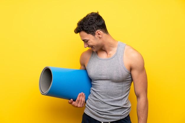 Uomo bello di sport sopra la parete isolata con la stuoia