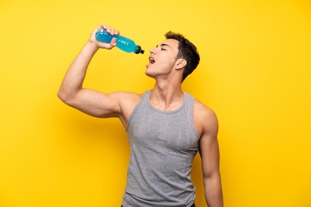 Uomo bello di sport sopra la parete isolata con una bottiglia di soda