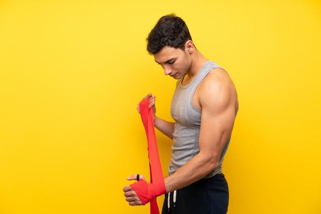 Uomo bello di sport sopra la parete isolata in fasciature di pugilato
