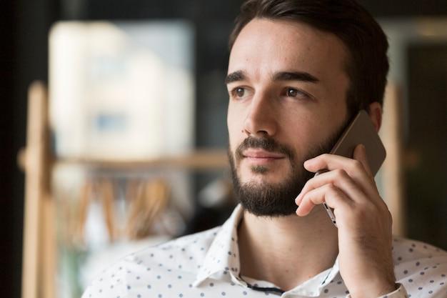Uomo bello di vista frontale che parla sopra il telefono