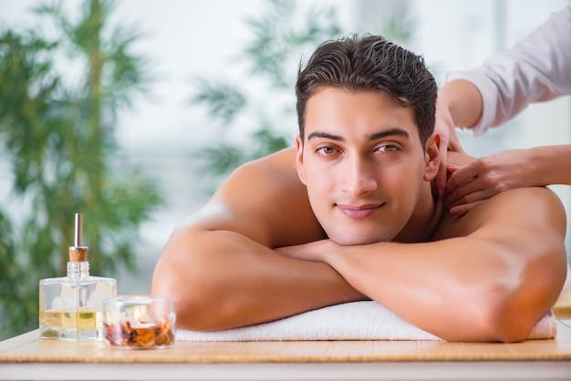 Uomo bello durante la sessione di massaggio spa