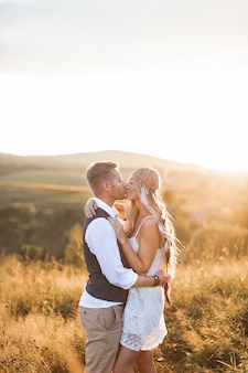 Uomo bello e bella donna in abiti rustici boho elegante, baciare