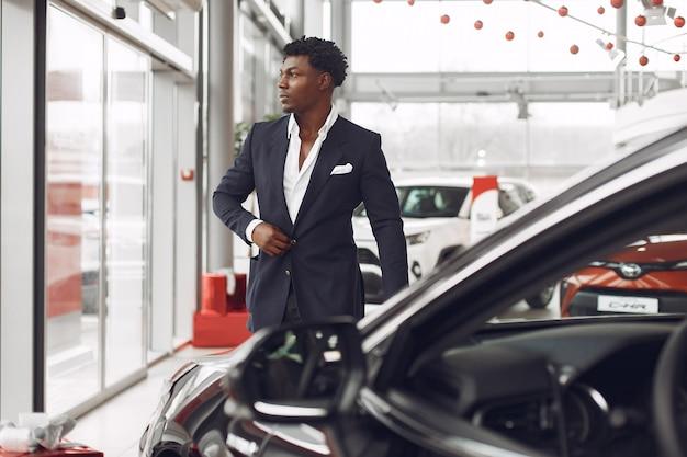 Uomo bello ed elegante in un salone di auto