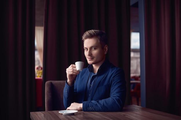 Uomo bello elegante con una tazza di caffè