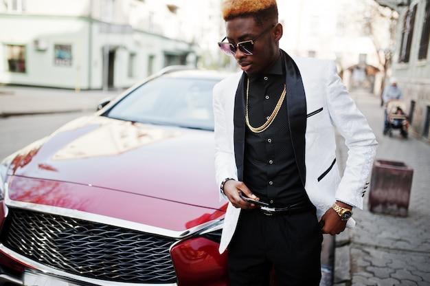 Uomo bello elegante in vestito bianco contro l'automobile di lusso rossa con il telefono cellulare a portata di mano.