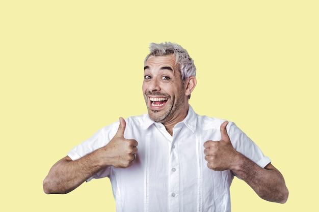 Uomo bello felice che mostra i pollici in su