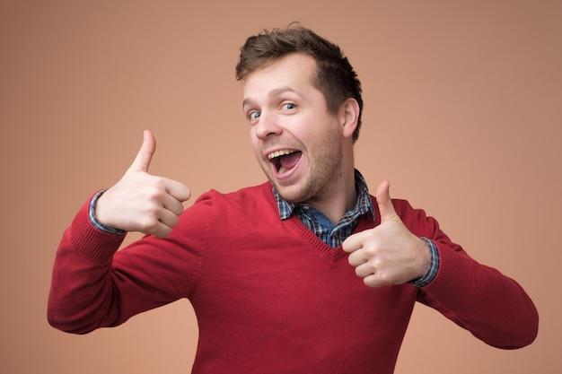 Uomo bello felice in maglione rosso che mostra i pollici in su