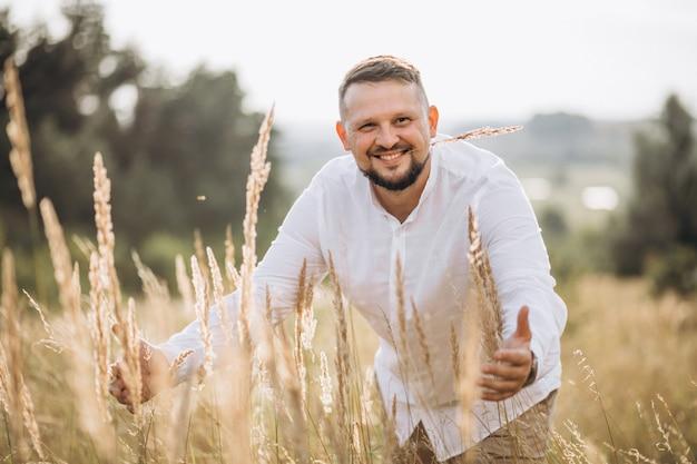 Uomo bello fuori in un campo dorato