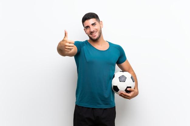 Uomo bello giovane calciatore sopra il muro bianco isolato con il pollice in alto perché è successo qualcosa di buono