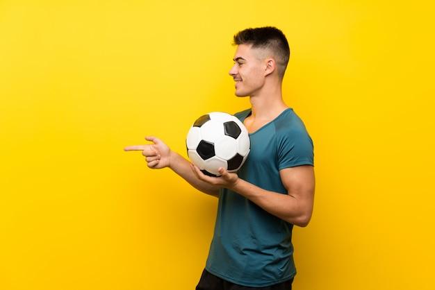 Uomo bello giovane calciatore sopra la parete gialla che punta verso il lato per presentare un prodotto