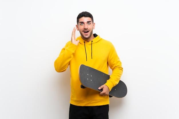 Uomo bello giovane del pattinatore sopra la parete bianca isolata con l'espressione facciale sorpresa e colpita