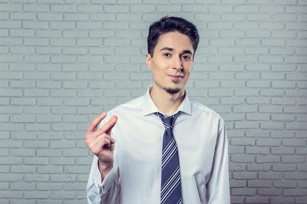Uomo bello in camicia bianca che smilling e schioccando le dita