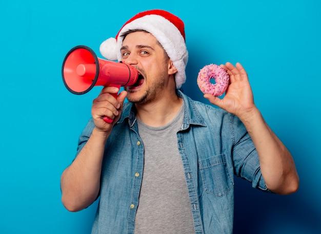 Uomo bello in cappello di natale con la ciambella e il megafono
