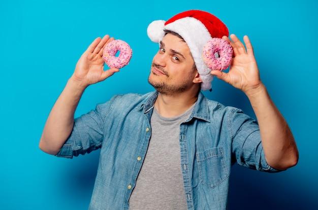 Uomo bello in cappello di natale con le ciambelle
