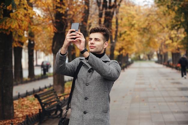 Uomo bello in cappotto che prende foto di bei alberi di autunno facendo uso del suo cellulare moderno mentre camminando nel parco vuoto