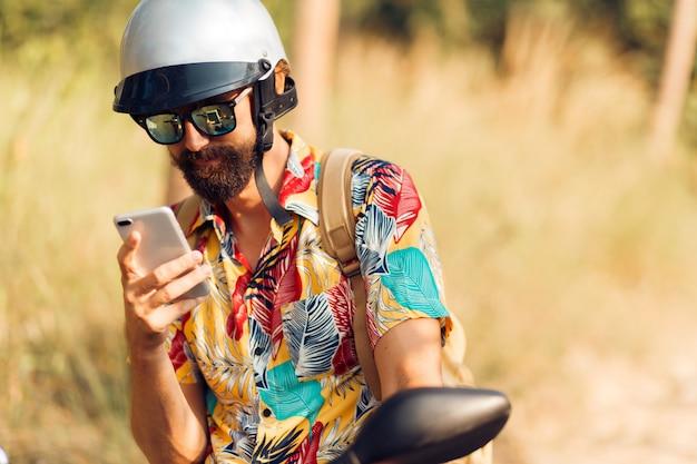 Uomo bello in casco che si siede sulla motocicletta e che per mezzo del telefono cellulare