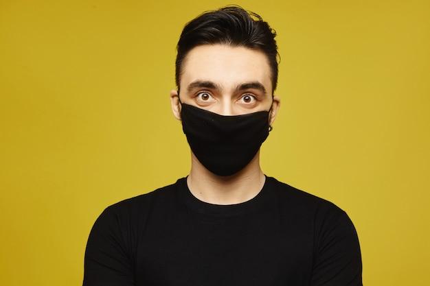 Uomo bello in maglietta nera e maschera protettiva nera isolati