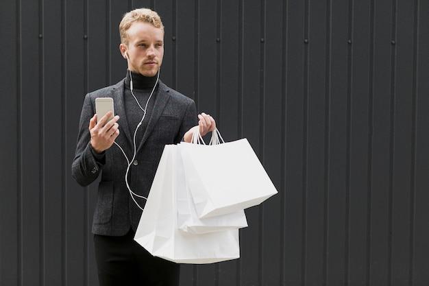 Uomo bello in nero con auricolari e smartphone