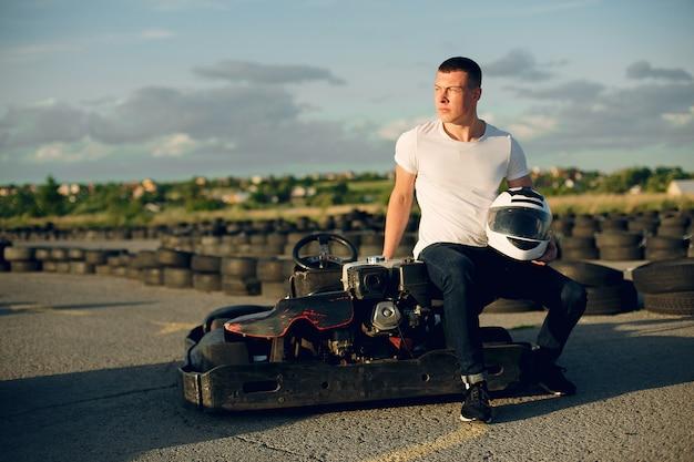 Uomo bello in un karting con un'auto