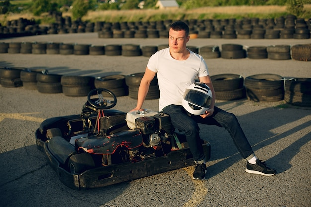 Uomo bello in un karting con un'auto