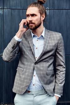 Uomo bello in vestito a quadretti grigio che parla con lo smartphone