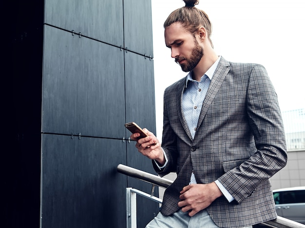 Uomo bello in vestito a quadretti grigio con lo smartphone