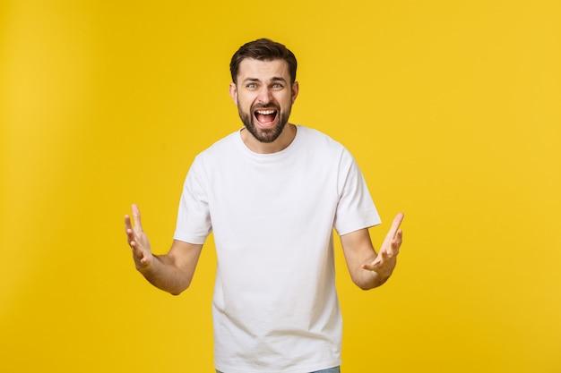 Uomo bello infelice del ritratto che esamina macchina fotografica su fondo giallo.