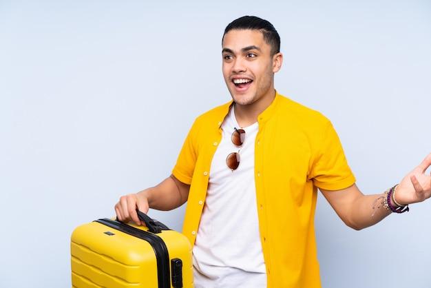 Uomo bello isolato sulla parete blu in vacanza con la valigia di viaggio e sorpreso