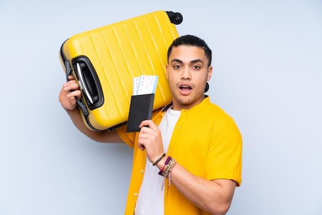 Uomo bello isolato sulla parete blu in vacanza con la valigia e passaporto e sorpreso