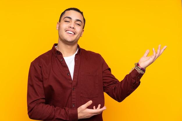 Uomo bello isolato sulla parete gialla che stringe le mani per chiudere molto