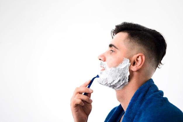 Uomo bello lateralmente che rade il suo primo piano della barba