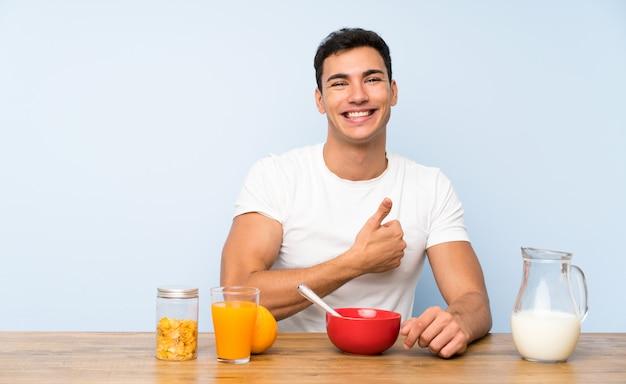 Uomo bello nel fare colazione dando un pollice in alto gesto