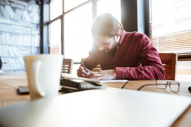 Uomo bello nel lavoro d'ufficio mentre scrivendo le note