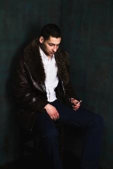 Uomo bello nel sedile di pelliccia nell'angolo e pensare