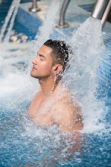 Uomo bello nella piscina per idroterapia