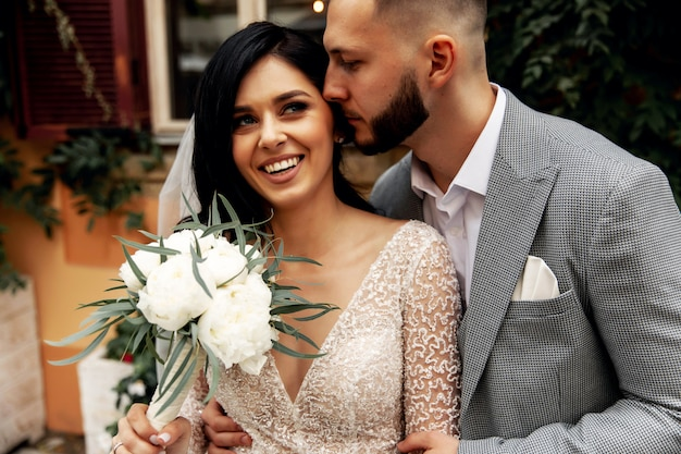 Uomo bello o sposo afroamericano che abbraccia ragazza graziosa o sposa sveglia con bei capelli biondi in vestito da sposa sexy bianco all'aperto sul fondo vago della via della città