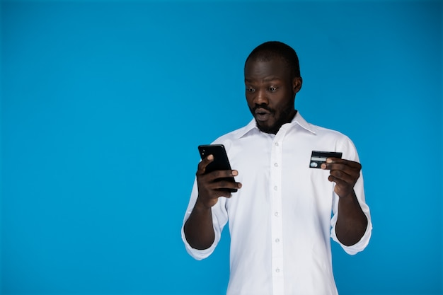 Uomo bello piacevolmente sorpreso con una carta di credito e un telefono