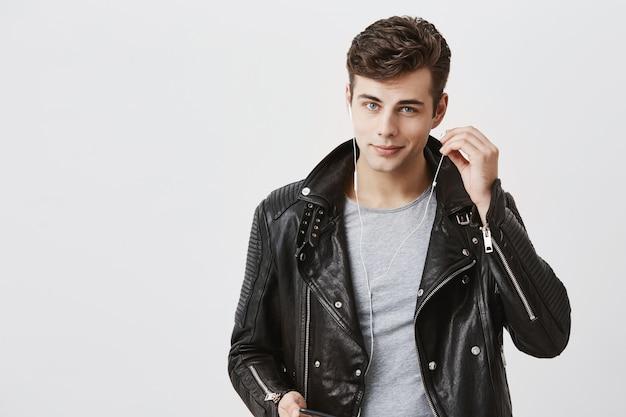 Uomo bello positivo in giacca di pelle nera con un debole sorriso, ascolta musica in cuffia. il giovane maschio caucasico gode di piacevoli melodie, indossa cuffie bianche e guarda con gli occhi blu.