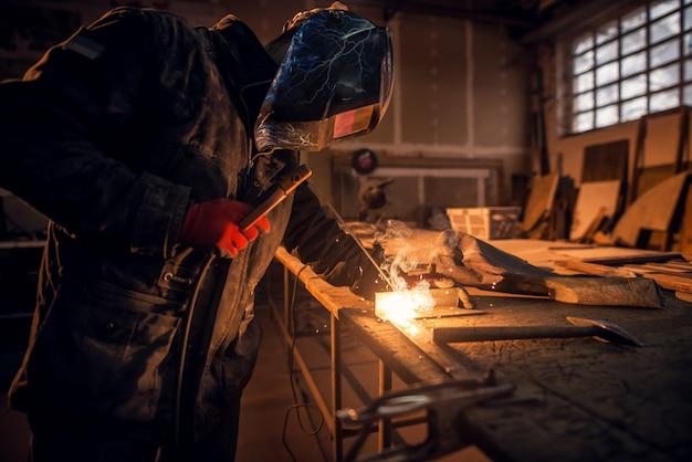 Uomo bello saldatore laborioso con maschera di protezione lavorando sulla struttura in acciaio in fabbrica mentre scintille volanti